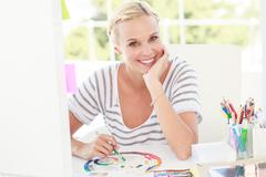 Happy designer working with a colour wheel Stock Photos