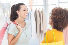 Two attractive friends laughing in a clothing store - stock photo