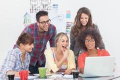 Cheerful team of creative designers working on a laptop Stock Photos