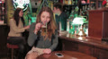 woman drink a beer in a pub and receives a phone call Footage