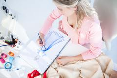 Stock Photo of Blonde fashion designer drawing clothes