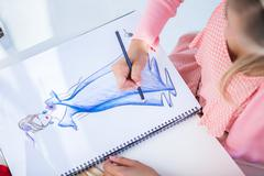 Fashion designer drawing clothes while she is sat at her desk Stock Photos