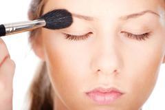 Woman applying make up with brush Stock Photos