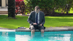 Businessman sitting by the poolside and working on tablet computer - stock footage