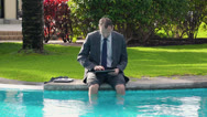 Stock Video Footage of Businessman sitting by the poolside and working on tablet computer