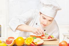 Stock Photo of chef decorating delicious fruit plate