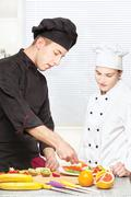 senior chef teaches young chef to decorate - stock photo
