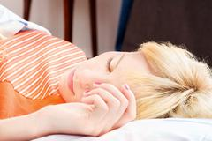 sleeping with hand on pillow - stock photo