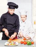 Senior chef teaches young chef to cut Stock Photos
