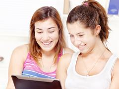 Happy teenage girls using touchpad Stock Photos