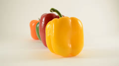 Yellow, Red, Green and Orange Peppers Against White - Dolly Right Stock Footage