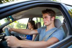 Driving: driver paying attention while passenger texts Stock Photos