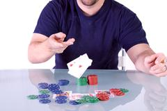 man throwing cards on the table in texas hold'em - stock photo