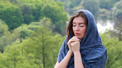 A brunette woman praying with her hands together - stock footage