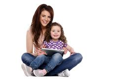 Mother and daughter using a computer tablet Stock Photos