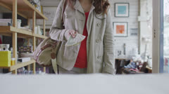 Close up of the payment transaction of a young woman at the store counter - stock footage