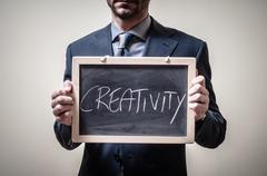 businessman holding blackboard written creativity - stock photo