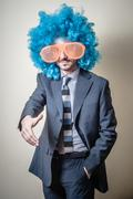 funny businessman with big orange glasses and blue wig - stock photo