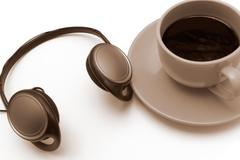 Isolated cup ofr coffee with headphones, in sepia Stock Photos