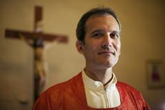portrait of happy catholic priest smiling at camera in church - stock photo