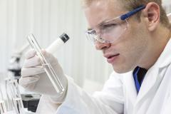 male scientist or doctor with test tube in laboratory - stock photo