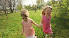 Sisters running around in garden and laughing Stock Footage