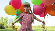 Stock Video Footage of Child spinning with balloons in the park and looking at camera