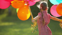 Child spinning with balloons in the park.  Girl looking at camera Stock Footage