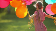 Stock Video Footage of Child spinning with balloons in the park.  Girl looking at camera