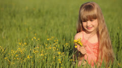 Cute child sitting on grass with flowers - stock footage