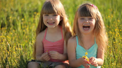 Children sitting in  field and laughing - stock footage