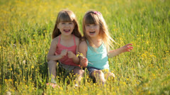 Cute kids sitting on grass and laughing - stock footage