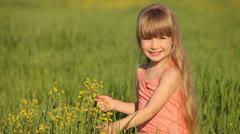 Kid sitting in field and picking flowers - stock footage