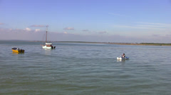 Leigh On Sea Man Rowing Past 2 Boats Stock Footage