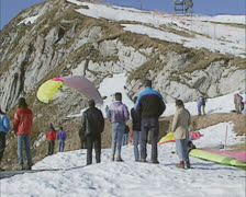 para-glider takes off from mountains - tracking shot - stock footage