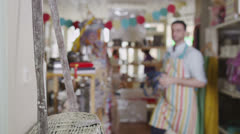 Male sales assistant or store owner is arranging the display items in his shop Stock Footage