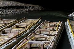 Natural bamboo rafts with passenger seats for river excurcions through tham l Stock Photos