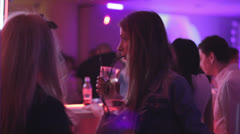 Young woman in night club drinking cocktails near the bar Stock Footage