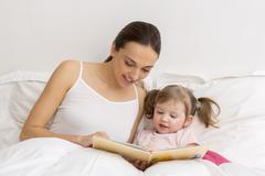 Child reading a book with her mother Stock Photos