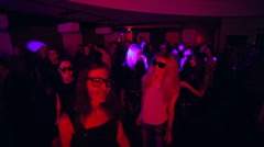 Men and women dance to sounds of music in night club. Jib shot Stock Footage