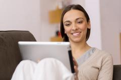 Woman sitting on sofa with tablet pc Stock Photos
