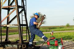 worker with pipe wrench on oilfield pipeline - stock photo