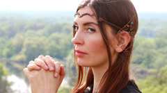 Beautiful elf in a profile, holds hands in the face of, as at a prayer Stock Footage