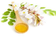 honey in spoon with acacia flower - stock photo