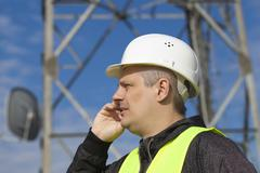 Engineer talking on the cell phone near to gsm tower - stock photo