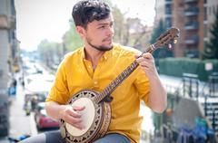Hipster nuori mies pelissä banjo Kuvituskuvat