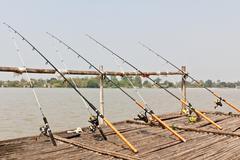 fishing poles on pier - stock photo