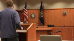 Man at podium in a empty courtroom Stock Footage