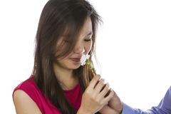 Woman smellng a flower given by her lover Stock Photos
