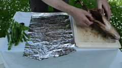 Speed up hands wrap big fish into foil for baking in fire ember Stock Footage